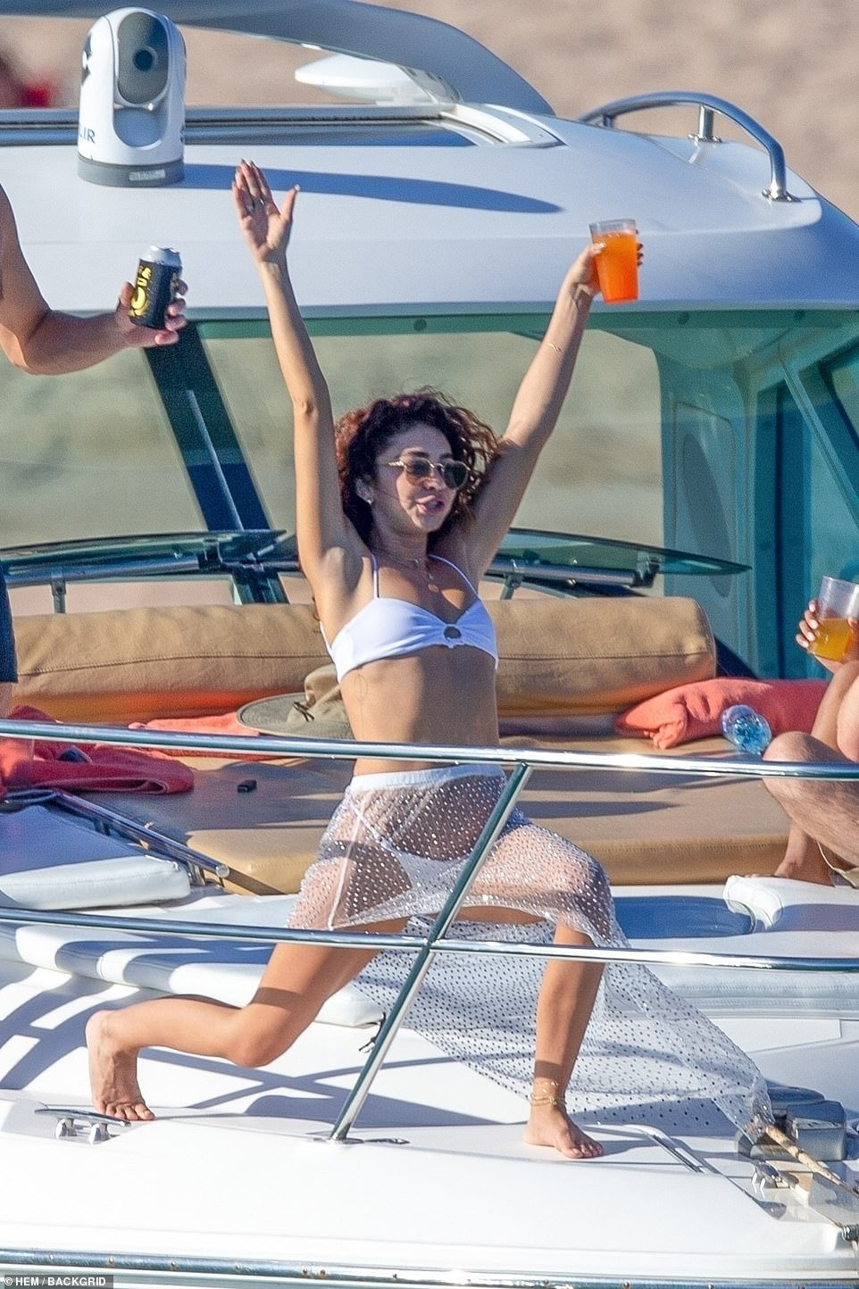Put your hands in the air like you just don't care! The actress lunged towards the floor and raised her drink into the air