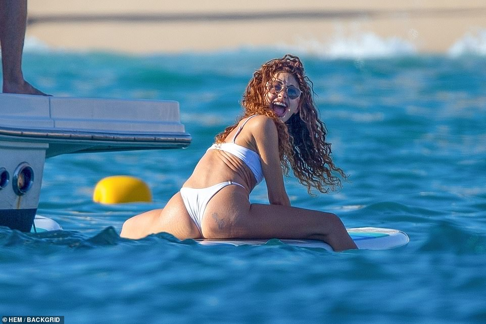 Fun in the sun! The bikini-clad star couldn't have looked happier paddling out into the ocean
