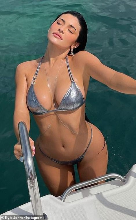 In the heat:The makeup mogul's figure looked flawless as she made the most of a silver bikini while climbing up the back of a yacht with crystal blue water behind her suggesting she was in the tropics