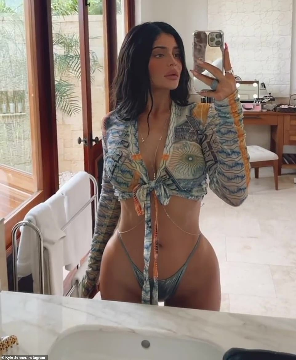 Now in her hotel room: In this image, she added a cover up with a blue and white design that tied in front