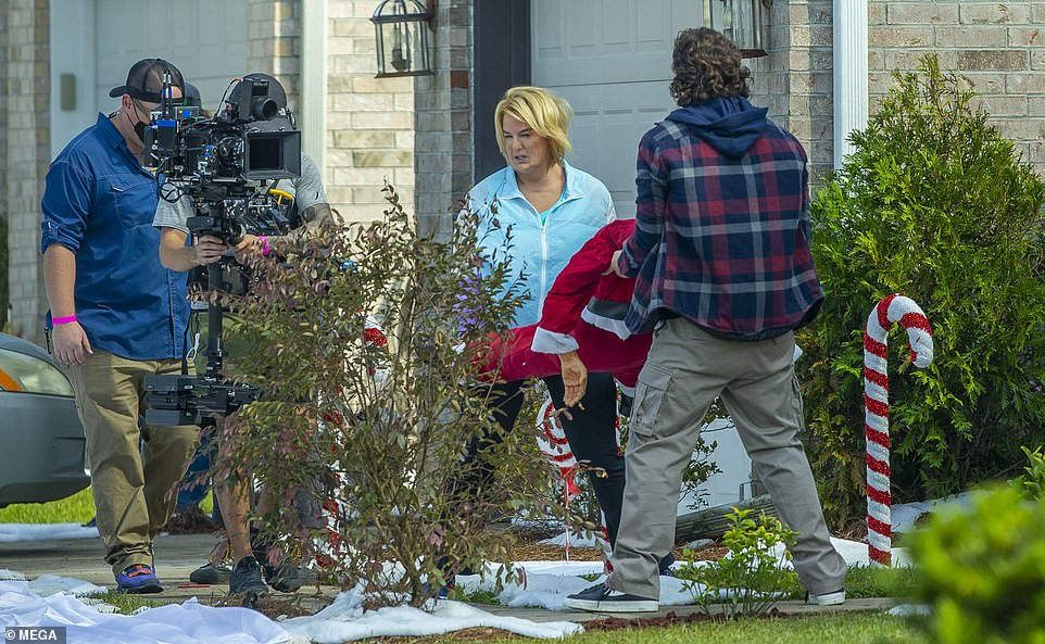 Setting it up: After they got the eerily lifelike Christmas decoration on its feet next to a giant candy cane, the Bridget Jones' Diary star was seen kneeling down as she adjusted it