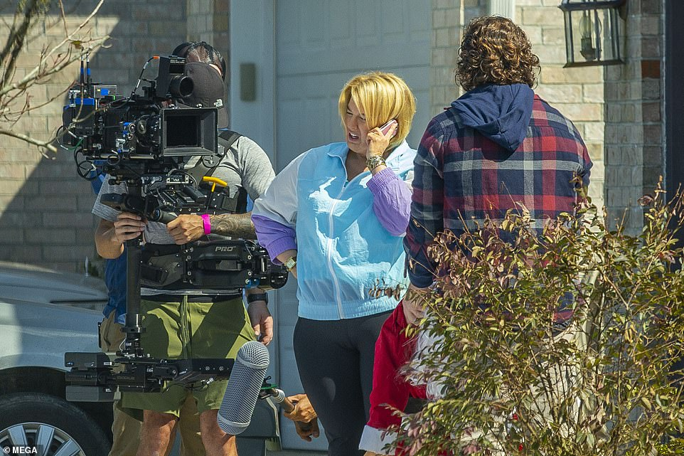 Tight: She was seen filming the scene in a baby blue, white and lavender windbreaker, which she wore with black flared sweatpants. The clothes hugged her extra padding, and she rounded out the costume with a pair of blue Asics trainers.